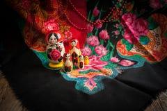 Matryoshka and headscarf. Matryoshka on a background of patterned headscarf Stock Photo