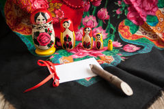 Matryoshka and headscarf. Matryoshka on a background of patterned headscarf and white card Stock Photo