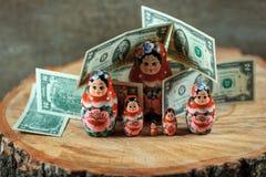 Matryoshka konst Rysk docka med dollar Anti-krissparbössa arkivfoton