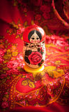 Matryoshka and red patterned headscarf. Matryoshka on a background of red patterned headscarf Royalty Free Stock Images