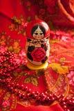 Matryoshka and red patterned headscarf. Matryoshka on a background of red patterned headscarf Stock Image