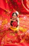 Matryoshka and red patterned headscarf. Matryoshka on a background of red patterned headscarf Royalty Free Stock Photos