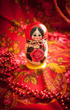 Matryoshka and red patterned headscarf. Matryoshka on a background of red patterned headscarf Stock Images