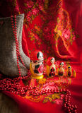 Matryoshka and red patterned headscarf. Matryoshka, boots, and beads against a red kerchief Royalty Free Stock Photo