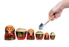 Matryoshkas full of coins and hand with shovel. Three Matryoshkas full of coins and hand holding shovel at white background Royalty Free Stock Images