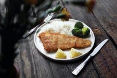 matställe Fisk i brödsmulor som stekas med ris och broccoli arkivfoton