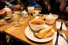 Matställe med vänner i restaurangen med ministronisoppa, bröd, sallad och öl royaltyfri bild