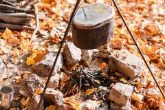 Matställekockar i en stor kruka över ett öppet avfyrar höstlig skog Royaltyfri Bild