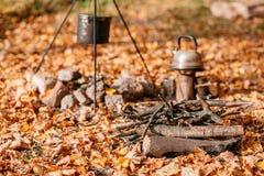 Matställekockar i en stor kruka över ett öppet avfyrar höstlig skog Royaltyfria Bilder
