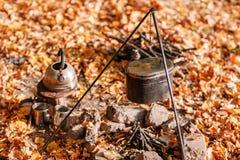 Matställekockar i en stor kruka över ett öppet avfyrar höstlig skog Arkivfoton