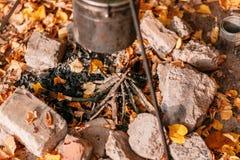 Matställekockar i en stor kruka över ett öppet avfyrar höstlig skog Royaltyfri Foto