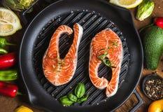 Matställematlagningingredienser Två stycken av den rå okokta laxen med grönsaker, örter, citron, avokado, kronärtskockor, kryddor fotografering för bildbyråer