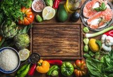 Matställematlagningingredints Rå okokt laxfisk med grönsaker, ris, örter och kryddor över lantligt trä Fotografering för Bildbyråer