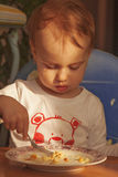 Matställen behandla som ett barn lite flickan äter pannkakor med ost royaltyfria bilder