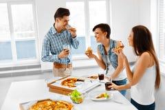 Matställeparti Lyckliga vänner som äter pizza och att ha gyckel kamratskap Arkivbilder