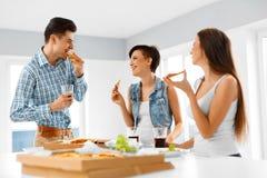 Matställeparti Lyckliga vänner som äter pizza och att ha gyckel kamratskap Arkivfoton