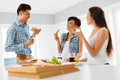 Matställeparti Lyckliga vänner som äter pizza och att ha gyckel kamratskap Fotografering för Bildbyråer