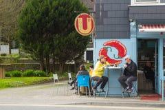 Matställetagandefördel av det tidiga vårsolskenet, som de tar ett mellanmål utomhus i Kinsale i ståndsmässig kork, Irland royaltyfri fotografi