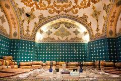 Matställeuppsättning i den orientaliska restaurangen som dekoreras med härliga persiska filtar och kuddar Arkivbilder