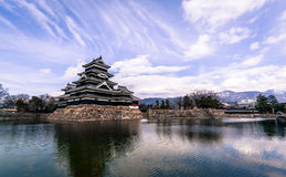 Matsumoto Castle and Moat, Japan. Matsumoto, Japan - March 06, 2015: View across the moat towards Matsumoto Castle with the Japanese Alps in the background Royalty Free Stock Photo