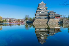 Matsumoto castle with red bridge, blue sky and reflection of the Royalty Free Stock Photos