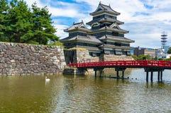 Matsumoto slott med den röda bron och vitsvanen på floden Royaltyfri Foto