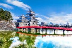Matsumoto slott mot med den röda träbron över kanalen I royaltyfri fotografi