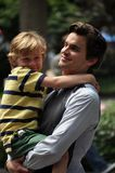 Matt bomer. This picture represents Matt Bomer at a break of shooting the TV series White Collar, holding his friend's son. It was taken in Manhattan, August Stock Photo