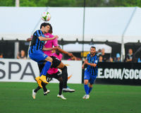Matt Dallman and Maikel Chang go to head the ball. Royalty Free Stock Images