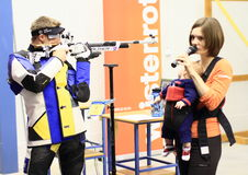 Matt and Katerina Emmons. Olympionic US representant Matt Emmons showing how to shoot with air gun while several Olympionic gold medal winner Katerina Emmons ( stock photo