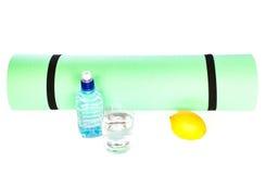 Matt rulle för yoga med flaskan av vatten på vit bakgrund Royaltyfria Bilder