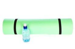 Matt rulle för yoga med flaskan av vatten på vit bakgrund Arkivbilder