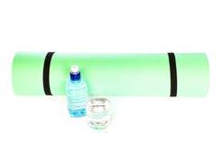 Matt rulle för yoga med flaskan av vatten som isoleras på vit Arkivbild