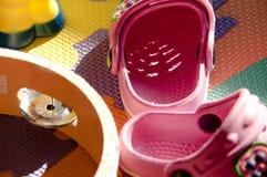 Matta av barn med ovannämnda små skor och leksaker Arkivbild