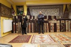 Matta säljaren som erbjuder färgrika orientaliska mattor på hans lager Royaltyfri Foto
