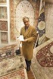 Matta säljaren som erbjuder färgrika orientaliska mattor på hans lager Royaltyfria Foton