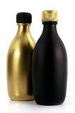 Matte black and gold bottles Stock Photos