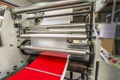 Matte or gloss plastic machine in a printing press for a perfect finish of printed documents. Matte or gloss plasticized machine in a printing press for a stock image
