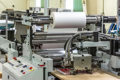 Matte or gloss plastic machine in a printing press for a perfect finish of printed documents. stock images