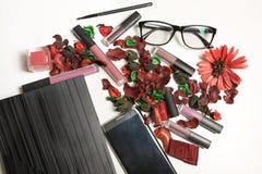 Matte lipstick kit, lip gloss, makeup brush and mobile phone ove. Matte lipstick kit, lip gloss, makeup brush and mobile phone on a white background Royalty Free Stock Images