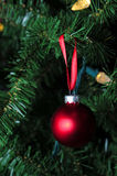 Matte red christmas ornament hanging on tree. With lights Stock Photo