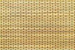 Matte von den gelben hölzernen Bambusstöcken mit braunem Thread Stockfoto