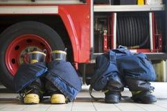 Matten und Hose des Feuerwehrmanns in einer Feuerwache Stockbild