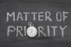 Matter of priority watch. Matter of priority phrase handwritten on chalkboard with vintage precise stopwatch used instead of O Royalty Free Stock Photography