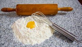Matterello della farina, frullino per le uova e tuorlo d'uovo II Fotografie Stock