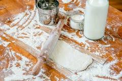 Matterello su una tavola decorata di legno coperta di farina al forno Pasta rotolata fra i bastoni per i rotolamenti Biscotto che fotografie stock