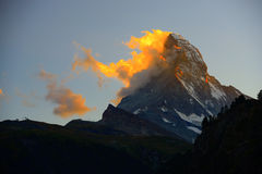 Matterhorn dans le début de la matinée avec l'alpenglow et le nuage sur la crête dedans Photographie stock
