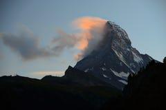 Matterhorn dans le début de la matinée avec l'alpenglow et le nuage sur la crête dedans Photos libres de droits
