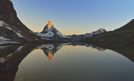 Matterhorn die in Riffelsee wordt weerspiegeld Stock Foto