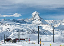 Matterhorn and the Gornergratbahn. ZERMATT – JANUARY 17: Red train climbing up to Gornergrat station with Matterhorn in the background on January 17, 2013 stock image